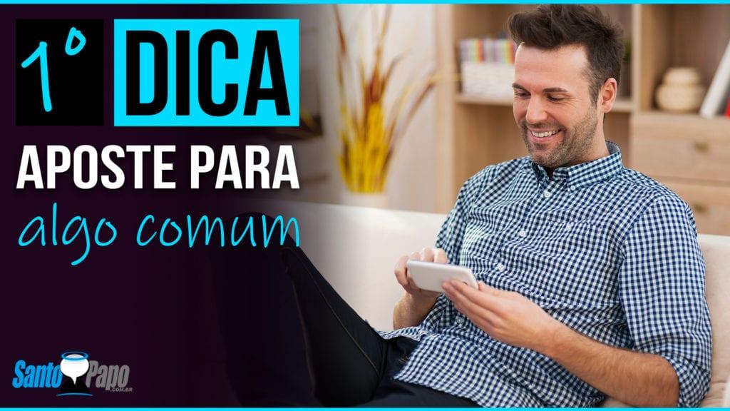 Homem sentado no sofá sorrindo enquanto olha para o celular