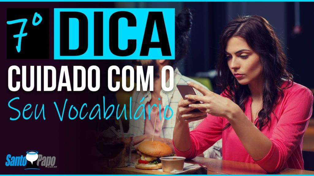 Mulher com cara de incomodada segurando seu celular em uma mesa de restaurante