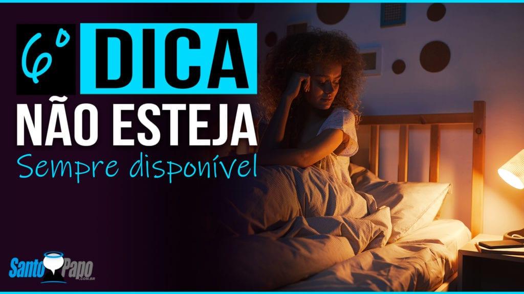 Mulher sentada em sua cama pensativa olhando para celular durante a noite